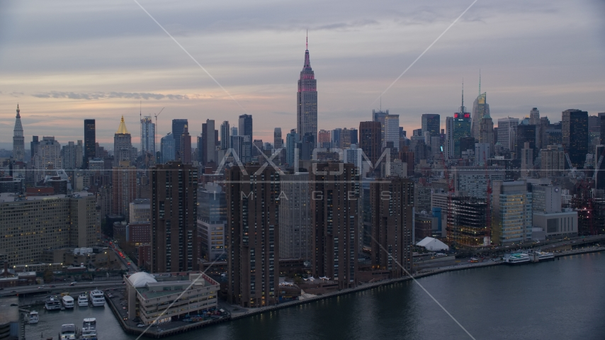 Empire State Building seen from riverfront apartment buildings at sunset in New York City Aerial Stock Photos | AX121_049.0000000F