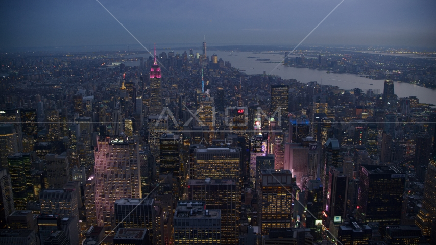Lights of Times Square and Midtown skyscrapers, Lower Manhattan towers in distance at sunset, New York City Aerial Stock Photo AX121_103.0000114F | Axiom Images