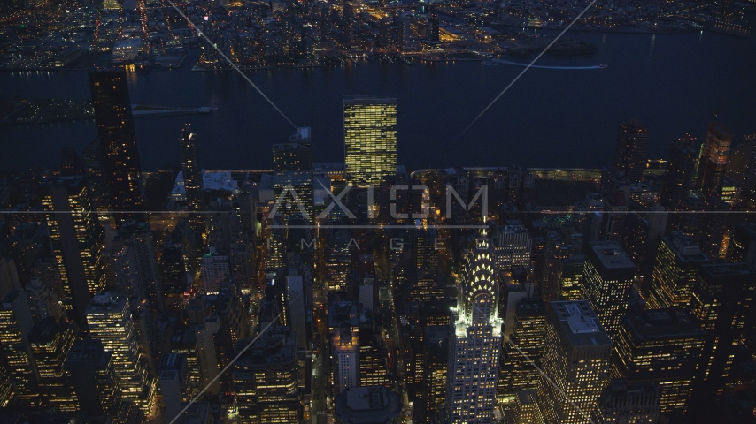 The United Nations and top of the Chrysler Building at night in New York City Aerial Stock Photos | AX121_138.0000000F