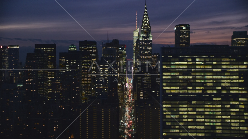 Midtown Manhattan city canyon by Chrysler Building and UN at night in New York City Aerial Stock Photos | AX121_151.0000084F