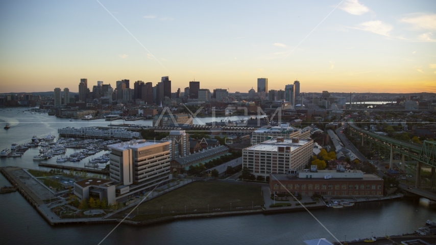 Office buildings in Charlestown, Massachusetts at sunset, and the Downtown Boston skyline Aerial Stock Photos | AX146_097.0000237F