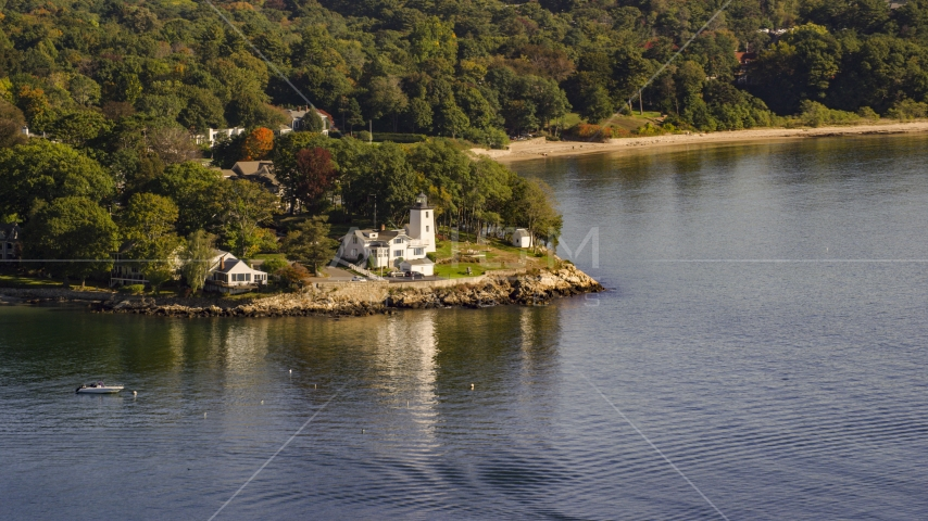 A lighthouse nestled among trees by cove, autumn, Beverly, Massachusetts Aerial Stock Photos | AX147_053.0000000