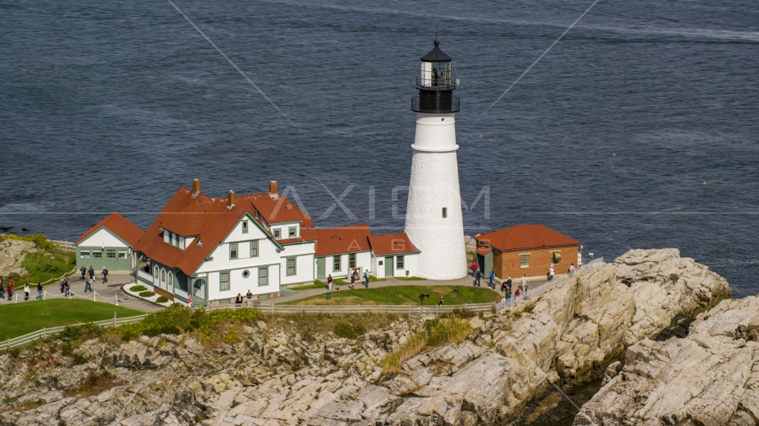 The Portland Head Light on a rocky shore overlooking the ocean in autumn, Cape Elizabeth, Maine Aerial Stock Photos | AX147_315.0000249