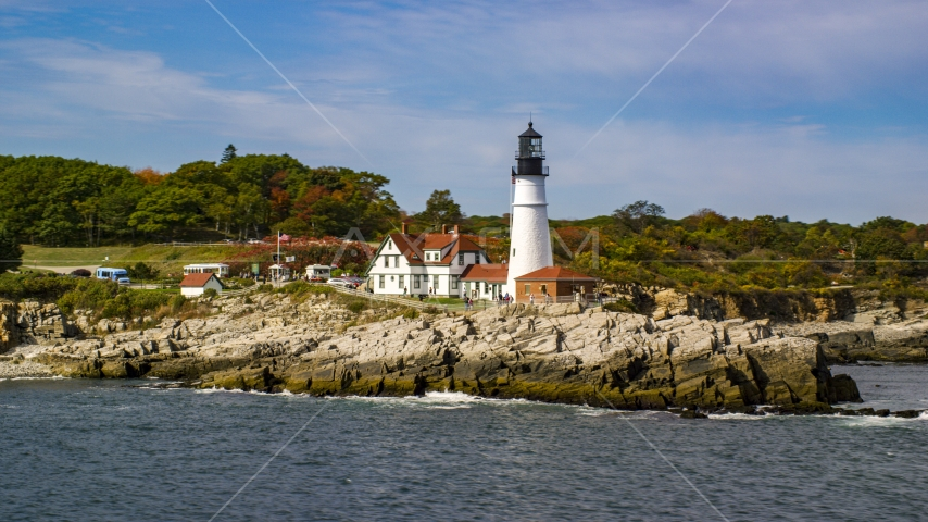 The Portland Head Light on a rocky shore, seen from the ocean in autumn, Cape Elizabeth, Maine Aerial Stock Photo AX147_316.0000190 | Axiom Images