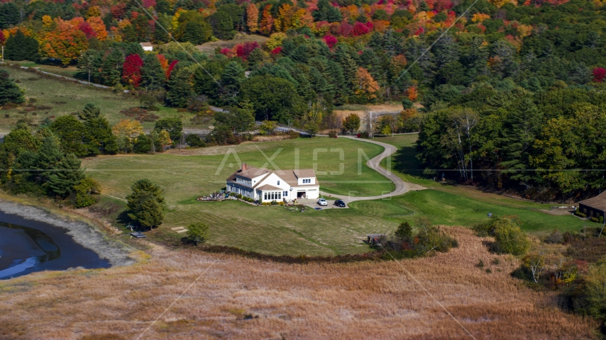 An isolated home and colorful autumn trees, Newcastle, Maine Aerial Stock Photos | AX148_011.0000000
