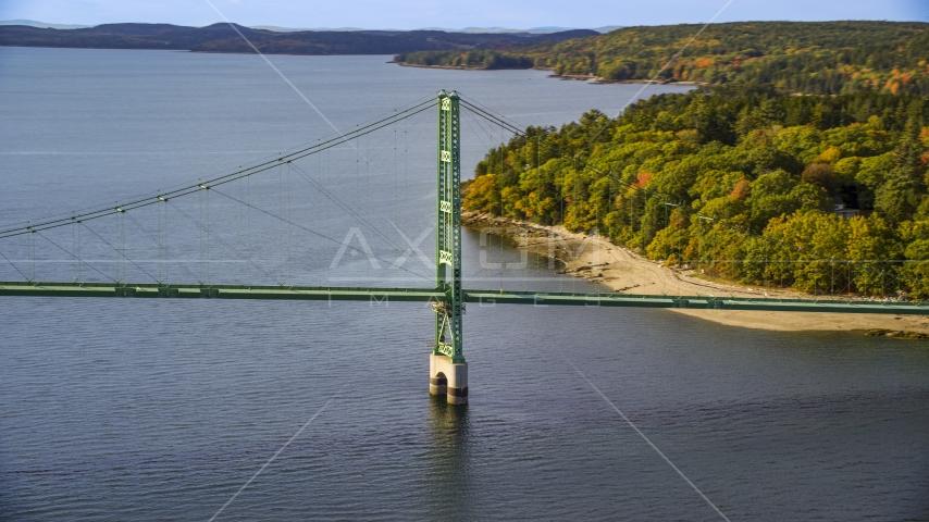 The Deer Isle Bridge near dense trees in autumn, Deer Isle Bridge, Maine Aerial Stock Photos | AX148_141.0000000