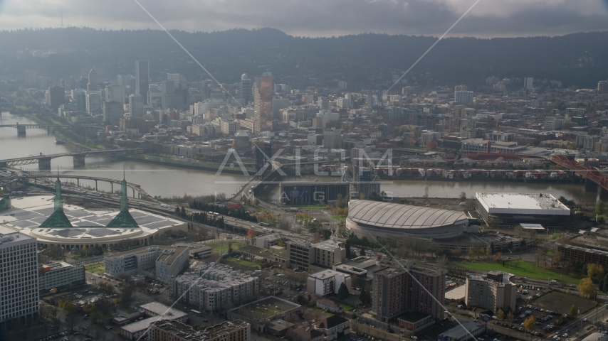 A view of Downtown Portland skyscrapers across the Willamette River from Moda Center in Oregon Aerial Stock Photos | AX153_112.0000311F