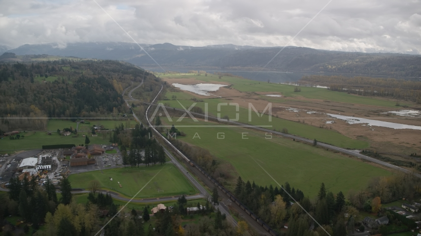 A train traveling by fields and country road in Washougal, Washington Aerial Stock Photos | AX153_177.0000000F