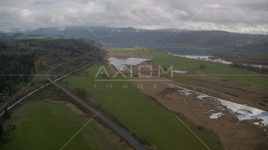 Train traveling by fields in Washougal, Washington Aerial Stock Photo AX153_177.0000272F | Axiom Images