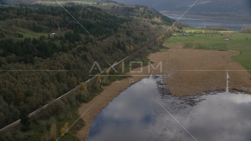 A train traveling by fields and water in Washougal, Washington Aerial Stock Photo AX153_178.0000113F | Axiom Images