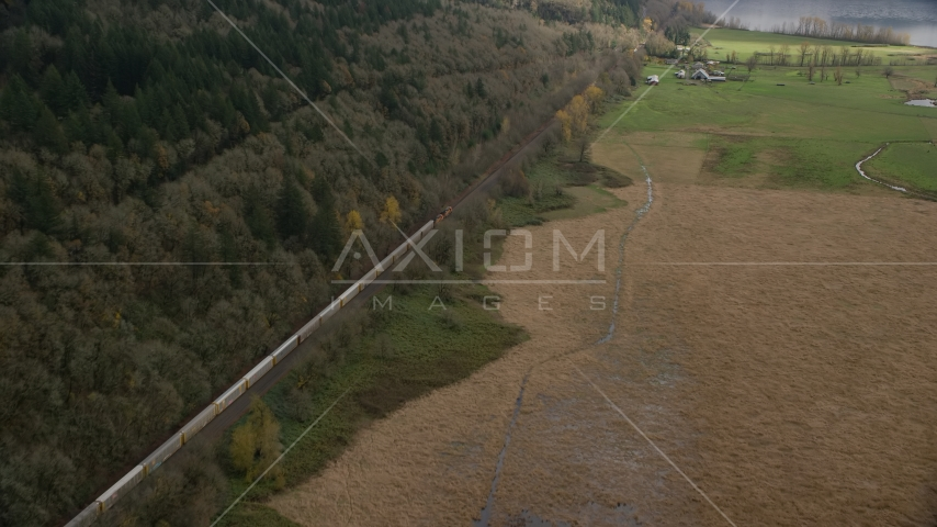A train traveling by fields and water in Washougal, Washington Aerial Stock Photo AX153_178.0000352F | Axiom Images