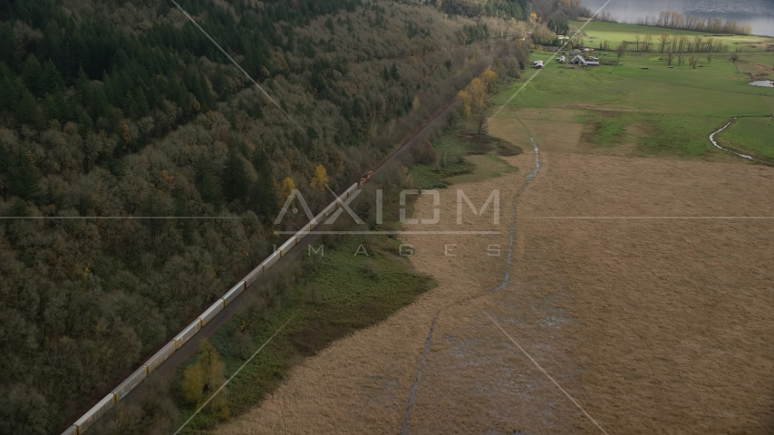 A train traveling past open farm fields in Washougal, Washington Aerial Stock Photos | AX153_179.0000000F