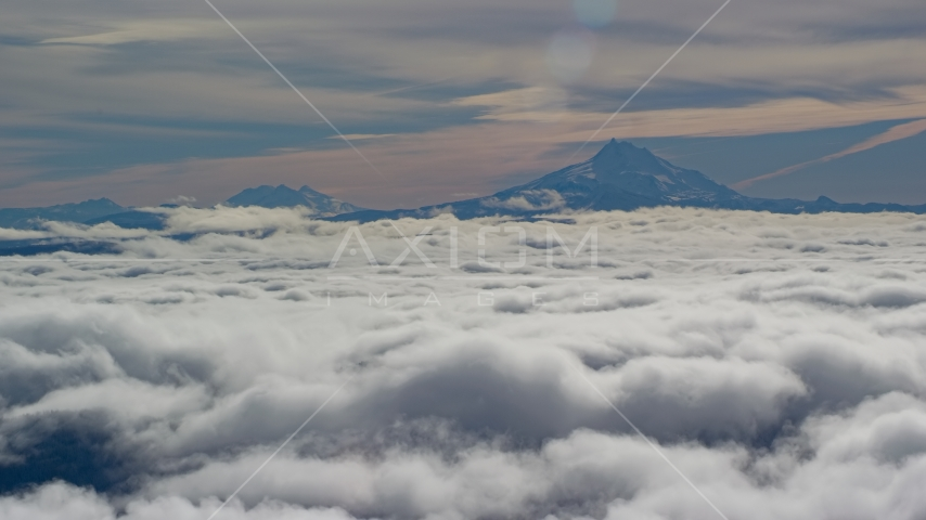Mount Jefferson and the Three Sisters Volcanoes seen from across low clouds, Cascade Range, Oregon Aerial Stock Photos | AX154_098.0000218F