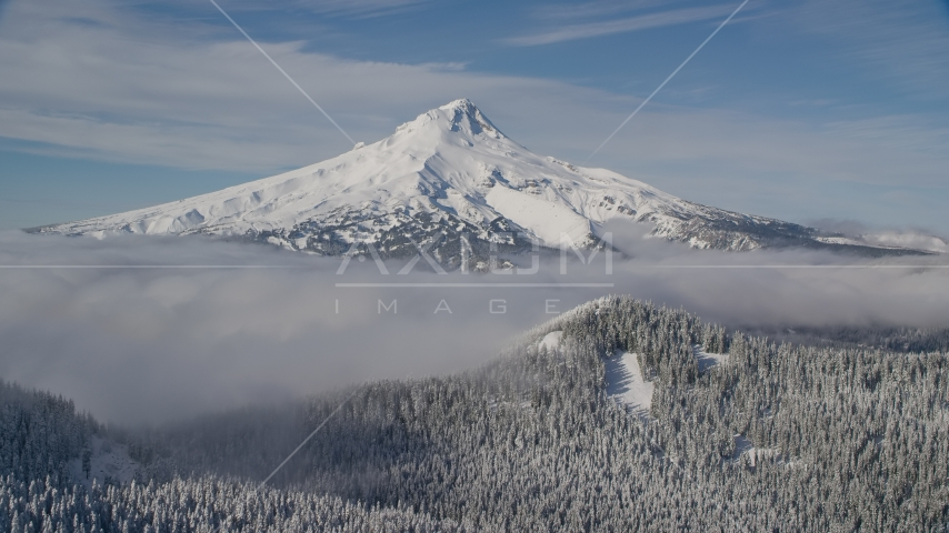 Mount Hood behind low clouds and snowy forest in the Cascade Range, Oregon Aerial Stock Photo AX154_112.0000000F | Axiom Images