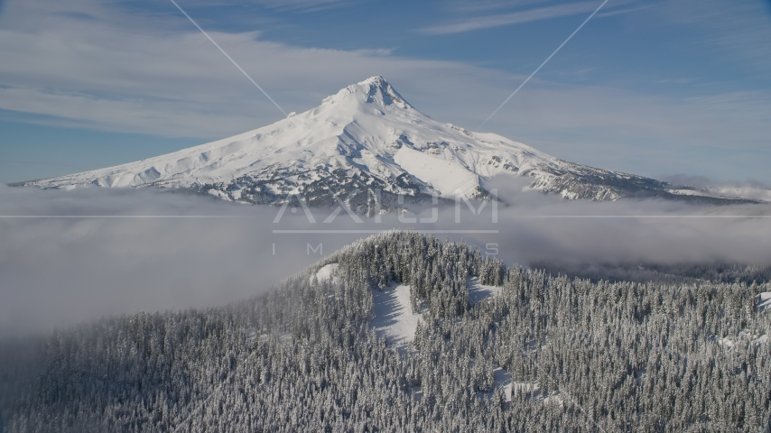 Mount Hood behind low clouds and a snow forest in the Cascade Range, Oregon Aerial Stock Photos | AX154_112.0000331F
