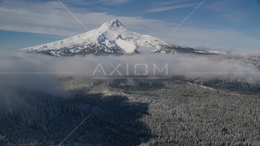 Snowy mountain peak with low clouds over forest, Mount Hood, Cascade Range, Oregon Aerial Stock Photo AX154_118.0000000F | Axiom Images