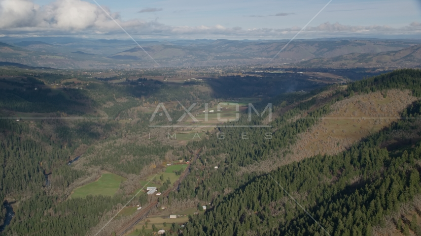 Farms and evergreen forest in a canyon, Hood River, Oregon Aerial Stock Photo AX154_148.0000145F | Axiom Images