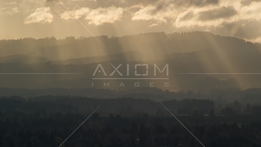 Godrays shining down on mountains near Beaverton, Oregon at sunset Aerial Stock Photos | AX155_124.0000225F