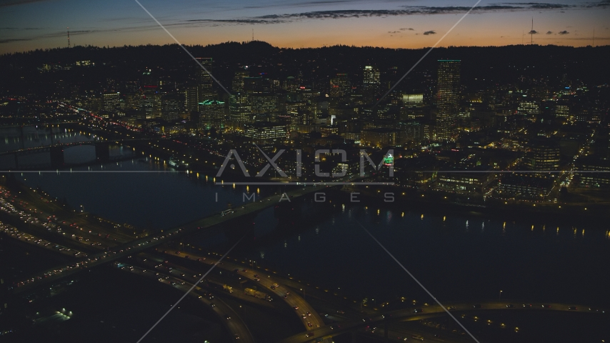 A view across the Willamette River of Downtown Portland and the White Stag Sign, Oregon, at night Aerial Stock Photo AX155_316.0000329F | Axiom Images