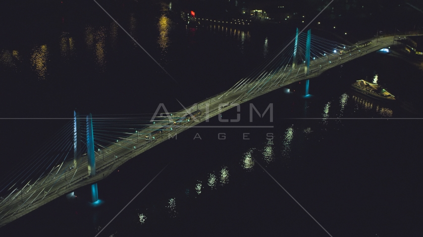 Tilikum Crossing bridge as a commuter train crosses the span at night in South Portland, Oregon Aerial Stock Photo AX155_416.0000264F | Axiom Images