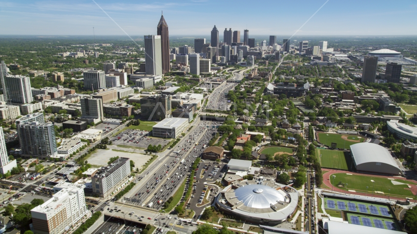 Alexander Memorial Coliseum along Downtown Connector toward Midtown Atlanta skyscrapers, Georgia Aerial Stock Photos | AX37_035.0000150F