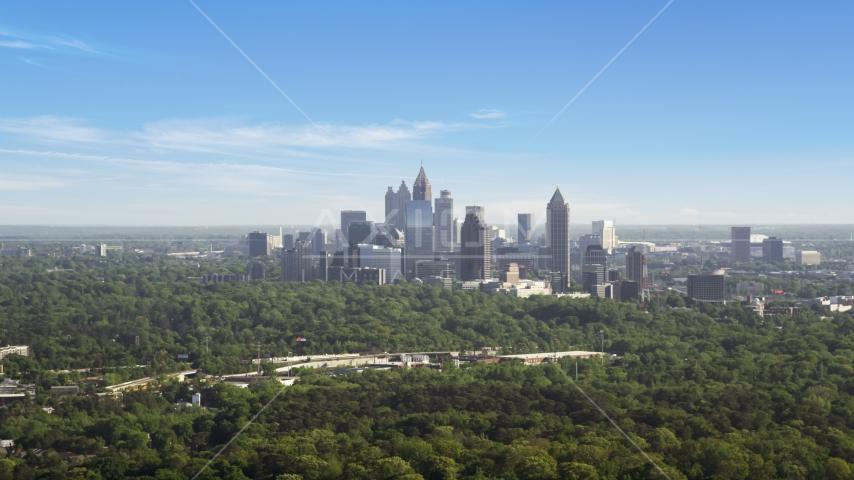 Distant shot of Midtown Atlanta skyscrapers beyond trees, Buckhead, Georgia Aerial Stock Photo AX38_027.0000048F | Axiom Images