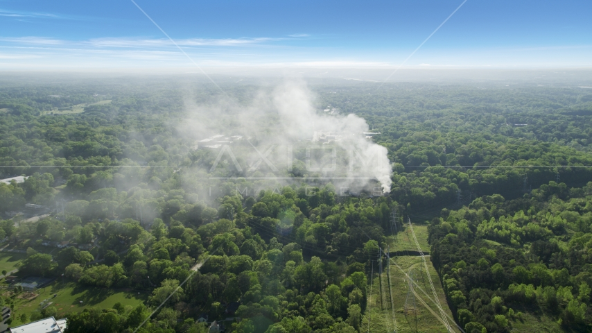 Smoke rising from a house fire in a wooded area, West Atlanta, Georgia Aerial Stock Photo AX38_048.0000129F | Axiom Images
