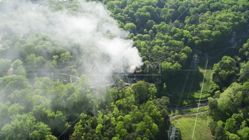 Smoke rising from a burning house in a wooded area, West Atlanta, Georgia Aerial Stock Photos | AX38_049.0000254F