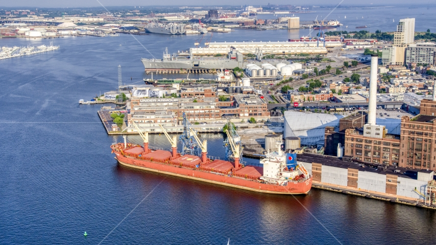 A cargo ship at Domino Sugar Factory, and waterfront factory buildings, Baltimore, Maryland Aerial Stock Photo AXP073_000_0014F   Axiom Images