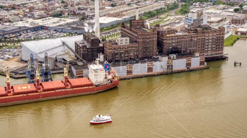 The Domino Sugar Factory and a docked cargo ship in Baltimore, Maryland Aerial Stock Photos | AXP078_000_0012F