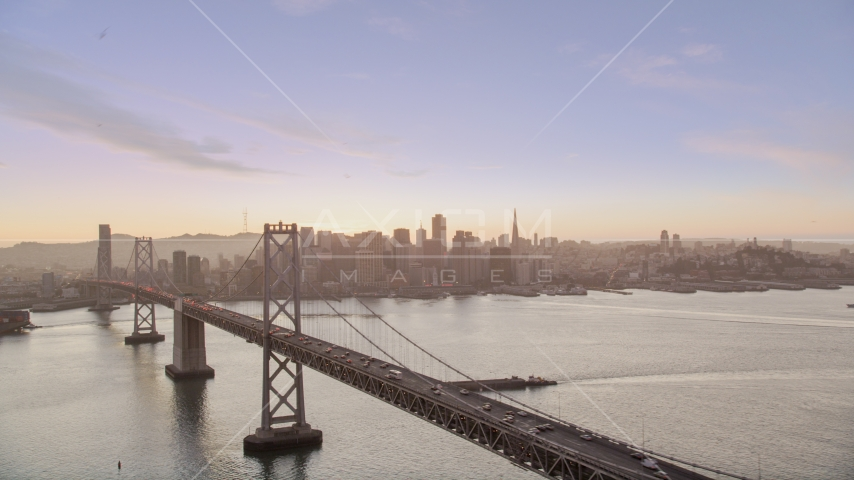 The Bay Bridge with a view of Downtown San Francisco skyline, California, twilight Aerial Stock Photo DCSF07_070.0000279 | Axiom Images