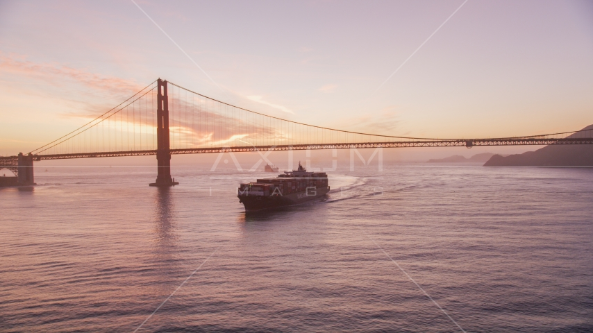 A cargo ship sailing by the Golden Gate Bridge, San Francisco, California, twilight Aerial Stock Photos | DCSF10_041.0000043