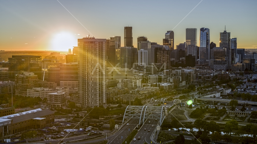 The rising sun behind the city's skyline and a residential skyscraper in Downtown Denver, Colorado Aerial Stock Photos | DXP001_000091