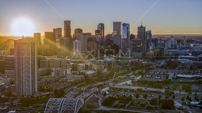 Sun rising behind the city's skyline and a residential skyscraper in Downtown Denver, Colorado Aerial Stock Photos | DXP001_000095
