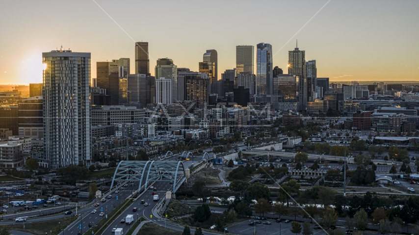 Sun rising behind residential skyscraper and city's skyline in Downtown Denver, Colorado Aerial Stock Photos | DXP001_000096