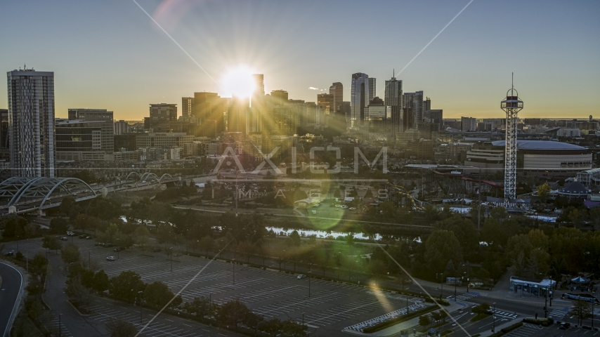 The city skyline with the bright sun behind the skyscrapers at sunrise in Downtown Denver, Colorado Aerial Stock Photos | DXP001_000102