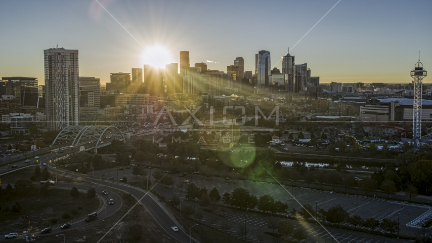 City's skyline with the sun behind the skyscrapers at sunrise in Downtown Denver, Colorado Aerial Stock Photos | DXP001_000104
