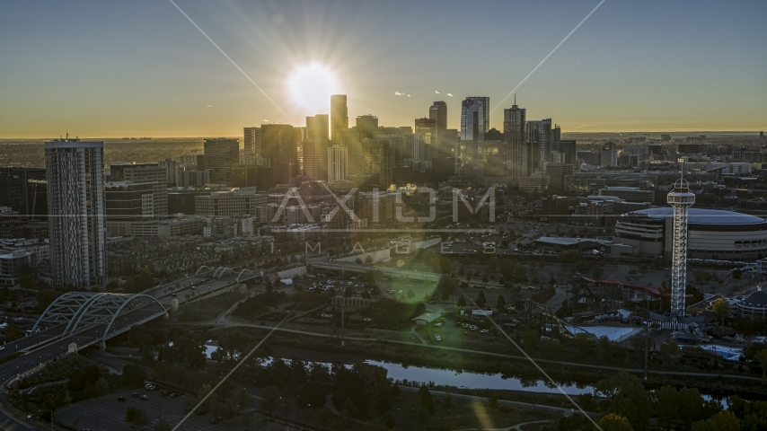 The sun shining behind the skyscrapers of the city's skyline at sunrise in Downtown Denver, Colorado Aerial Stock Photos | DXP001_000105