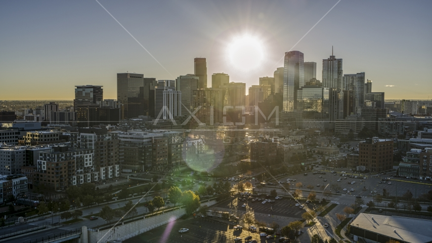 City's skyline with sun shining above skyscrapers at sunrise, Downtown Denver, Colorado Aerial Stock Photos | DXP001_000115