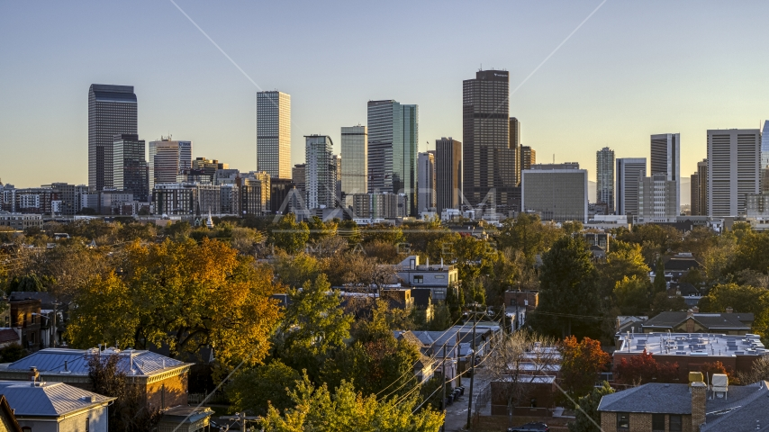 Wide view of city's skyline seen from tree-lined residential neighborhood at sunset, Downtown Denver, Colorado Aerial Stock Photos DXP001_000179