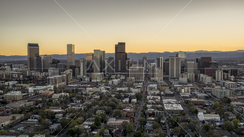 Wide view of skyscrapers in the city's downtown skyline at sunset, mountains in background, Downtown Denver, Colorado Aerial Stock Photos | DXP001_000185