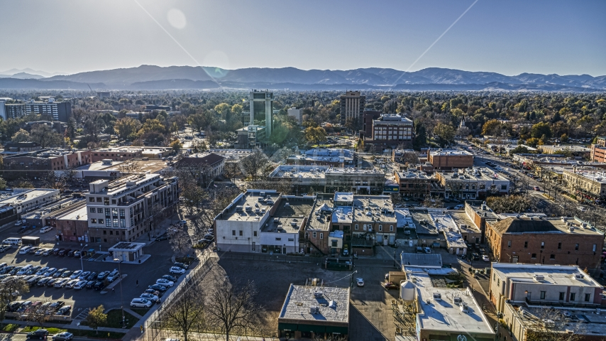 Shops with taller office buildings and mountains in the background in Fort Collins, Colorado Aerial Stock Photos | DXP001_000234