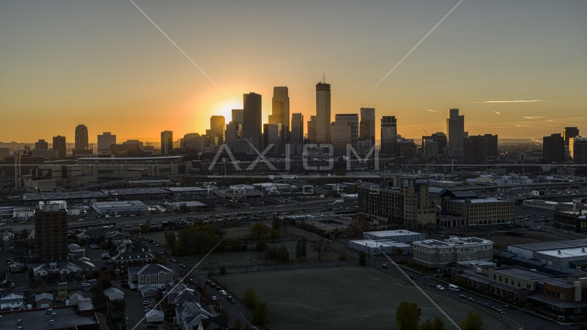The sun behind tall skyscrapers in the city's skyline at sunrise in Downtown Minneapolis, Minnesota Aerial Stock Photo DXP001_000257 | Axiom Images
