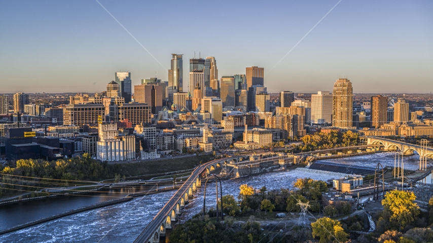The city's skyline seen from the Stone Arch Bridge spanning the river at sunrise, Downtown Minneapolis, Minnesota Aerial Stock Photo DXP001_000355 | Axiom Images