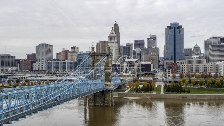 The side of the Roebling Bridge with the Ferris wheel and skyline in the distance, Downtown Cincinnati, Ohio Aerial Stock Photos | DXP001_000472