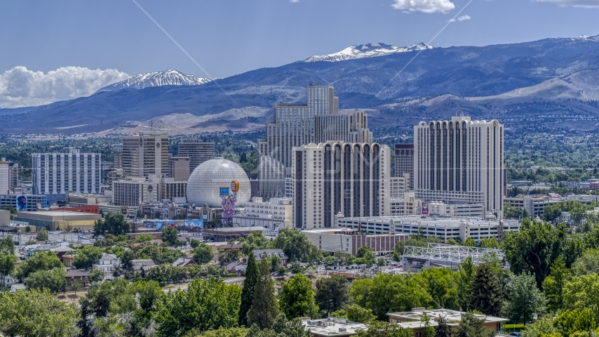 Hotels and casinos with mountains in the background in Reno, Nevada Aerial Stock Photos | DXP001_004_0004