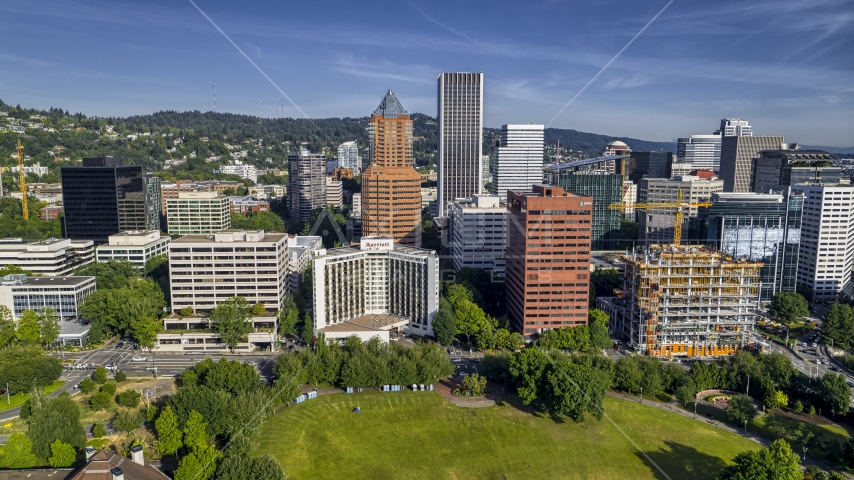 Marriott hotel flanked by taller office buildings and towering skyscrapers in Downtown Portland, Oregon Aerial Stock Photos | DXP001_011_0013