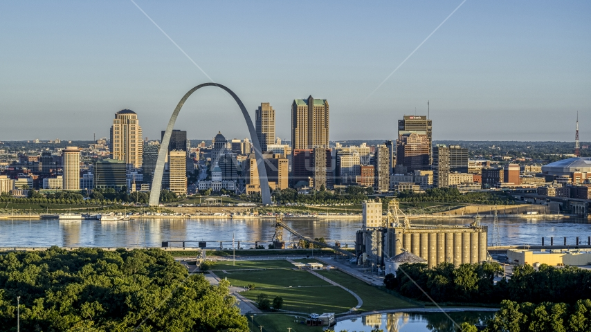 A grain elevator and park with a view of the Arch and skyline across the Mississippi River, sunrise, Downtown St. Louis, Missouri Aerial Stock Photos | DXP001_021_0006