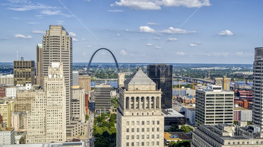 The Gateway Arch seen between skyscrapers and a courthouse tower in Downtown St. Louis, Missouri Aerial Stock Photos | DXP001_031_0007