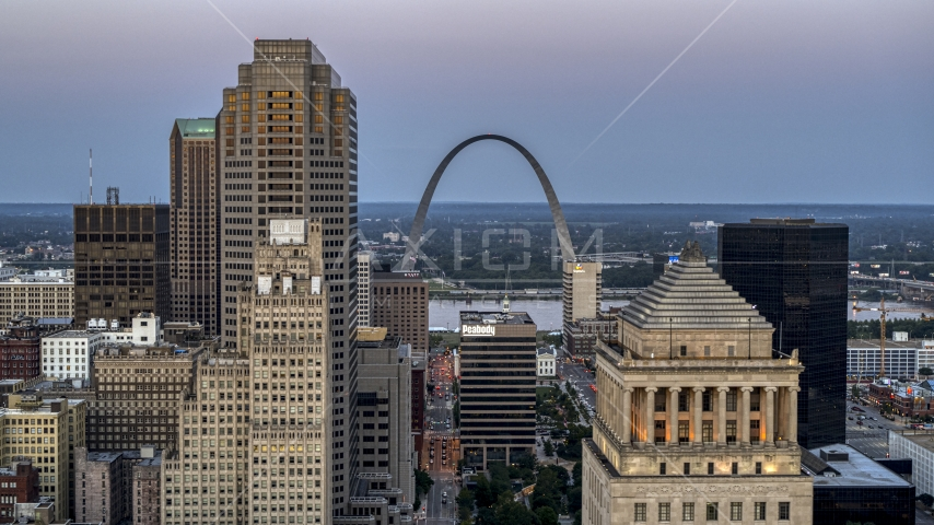 A view of the Gateway Arch between a skyscraper and a courthouse at twilight, Downtown St. Louis, Missouri Aerial Stock Photo DXP001_036_0011 | Axiom Images
